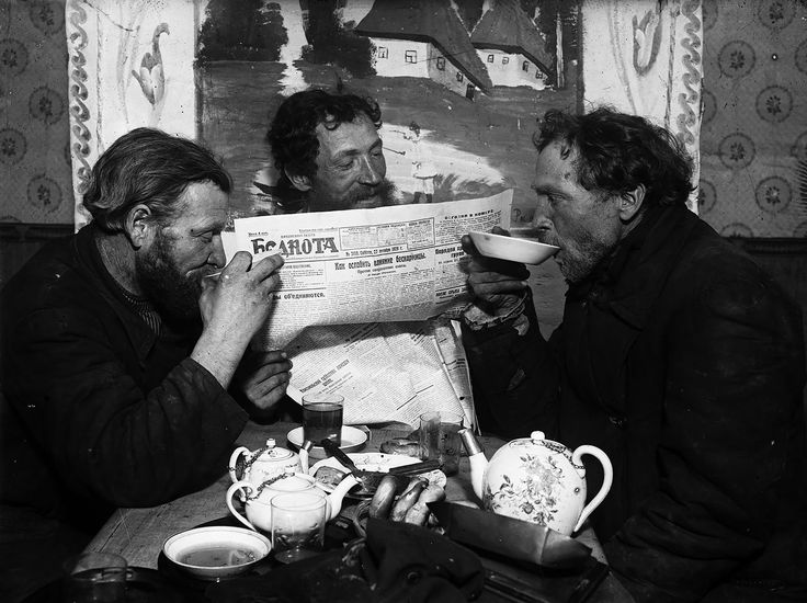 Tea­ drinking at Ramenskoye, 1928. Three bearded men at a village tea shack with a copy of the Bednota (Poor Folk) newspaper. On the table are Russian pretzels, snacks, and decorated tea pots. Ramenskoye, Moscow region.