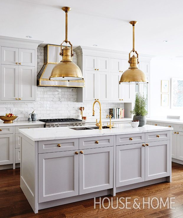 The brass details in this kitchen by designer Allison Willson make it hard to ignore; the way the majestic stainless steel range hood with brass trim ties the warm brass and cool grey cabinetry and marble together is worth noting. | Photographer: Angus Fergusson