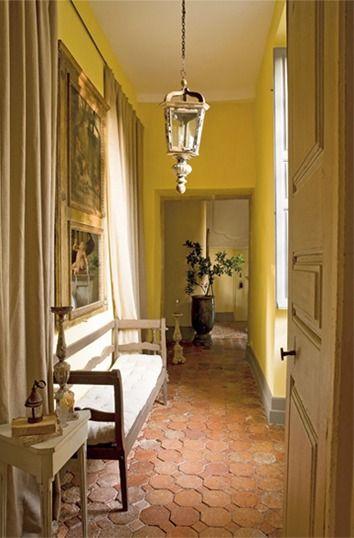 une belle tomette ancienne et un mur jaune ensoleille ce couloir qui fait provençal