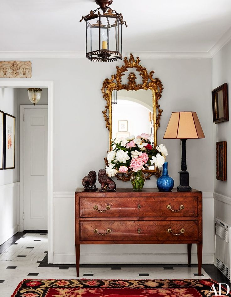 A French mirror hangs above an Italian commode in the entry hall.