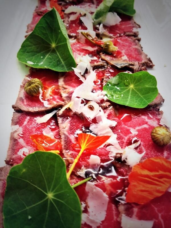 Sumac-cured carpaccio, wild oxeye daisy buds, nasturtium, liquid gold EVOO, parma from Chef Peter Angus at Shaw's Hotel on Prince Edward Island, Canada.