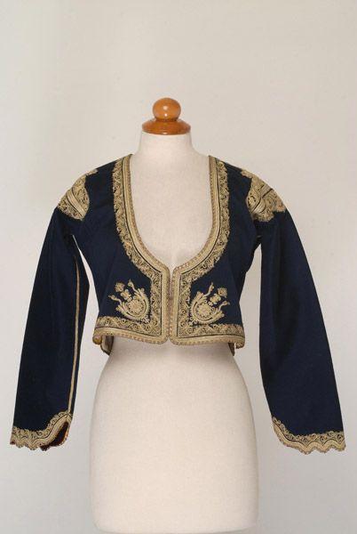 Μπλε τσόχινο ζιμπούνι, είδος μανικωτού ζακέτου, εξάρτημα της γυναικείας μεγαρίτικης φορεσιάς με φουστάνι.