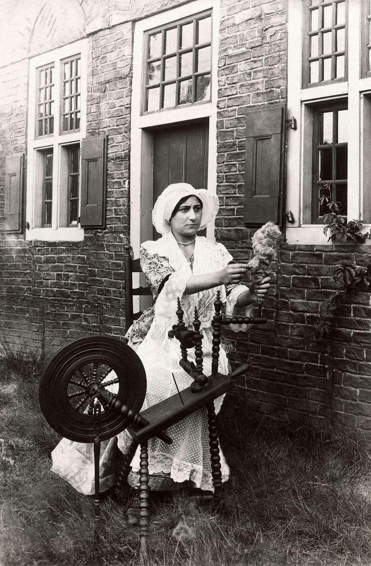 Steden en dorpen. Feestelijkheden in Laren(N-H). In het dorp is een decor van historische huizen opgebouwd. Voor éen ervan zit een vrouw in historisch kostuum die het gebruik van een spinnewiel demonstreert. Laren, Nederland, 1914. #Laren #Gooi #NoordHolland