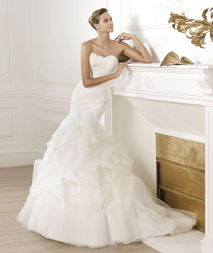 Vestido de novia drapeado de tul con escote palabra de honor de plumas. Falda corte sirena de volantes de tul con nylon.
