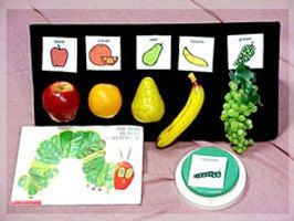 Velcro board with plastic fruit and picture symbols of fruit.  Concrete Symbolic: Matches/selects real objects, photos and symbols