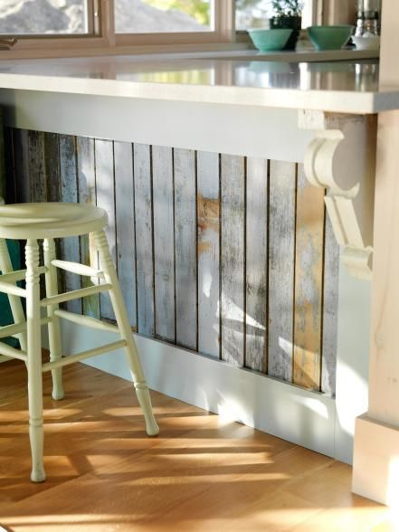 If you're handy with a saw, cut up found strips of weathered wood to give your kitchen island or peninsula a cottage-style facelift. Alternately, you can give new boards a similar look by painting them in different colors, then heavily sanding them.