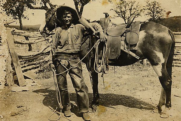 Judging by the saddle style, this unidentified cowboy was working in the late 1870s or 1880s. In his holster, he carries a Colt model 1873 single action revolver with hard rubber grips, and he has looped his left arm around a Winchester model 1873 carbine in a saddle scabbard. On the back is the light pencil inscription Indian fighter. :
