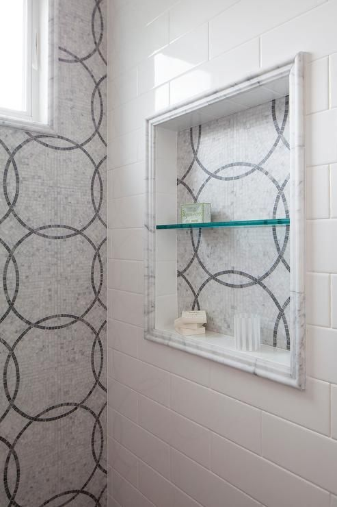 A stunning gray and white walk-in shower features a square shower niche fitted with a glass shelf and AKDO Eternity Tiles framed by white brick shower tiles accenting a wall fitted with floor to ceiling AKDO Eternity Tiles illuminated by a shower window.