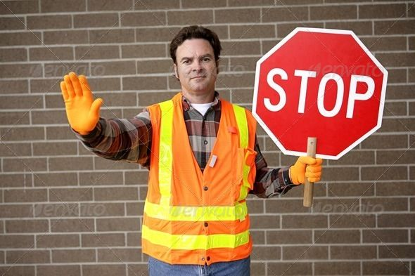 A friendly school crossing guard holding a stop sign.
