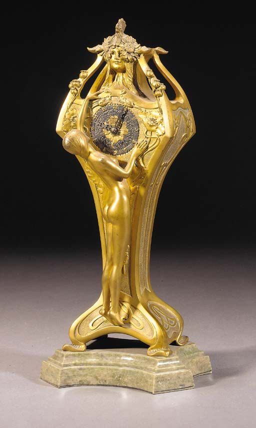 A GILT BRONZE FIGURAL MANTEL CLOCK cast from a model by L.Chalon, cast in relief with naked maiden stretching up towards Art Nouveau female mask above dial, the dial framed by wild poppies and scrolling vines, on a shaped green onyx base, signed in the bronze, stamped foundry mark 'M.Colin & Cie.' -- 36cm. high | CLASSIC ART NOUVEAU
