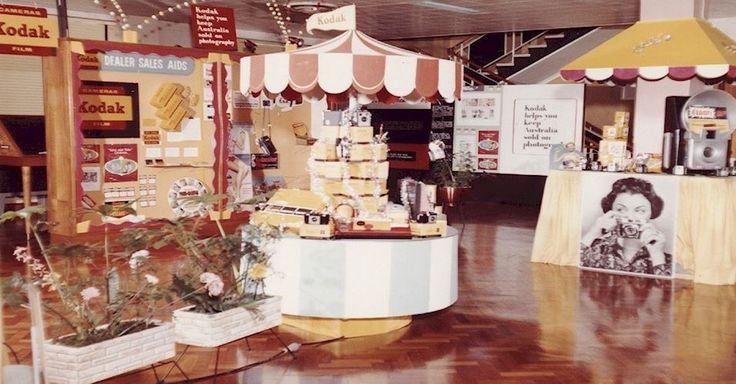 Colour photograph of a Kodak Australasia Pty Ltd wholesale trade display for dealers/industry in the 1960s. There is a board covered in different dealer sales aids. In the foreground are decorative pot plants and a stand filled with Kodak products. A board at the back of the room reads: 'Kodak helps you keep Australia sold on photography'.
