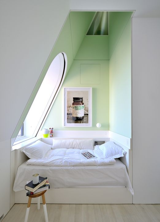 This four-level penthouse apartment in New York has some quieter moments (to contrast with the multistory reflective slide snaking throughout). Designed by architect David Hotson_Architect with interiors by Ghislaine Viñas, this top-floor bedroom is a minty moment of repose. Set into the dormer at the opposite side of the bedroom, the alcove bed occupies a wedge of space extending up to the attic-level oculus window. Photo: David Hotson.  Courtesy of David Hotson.
