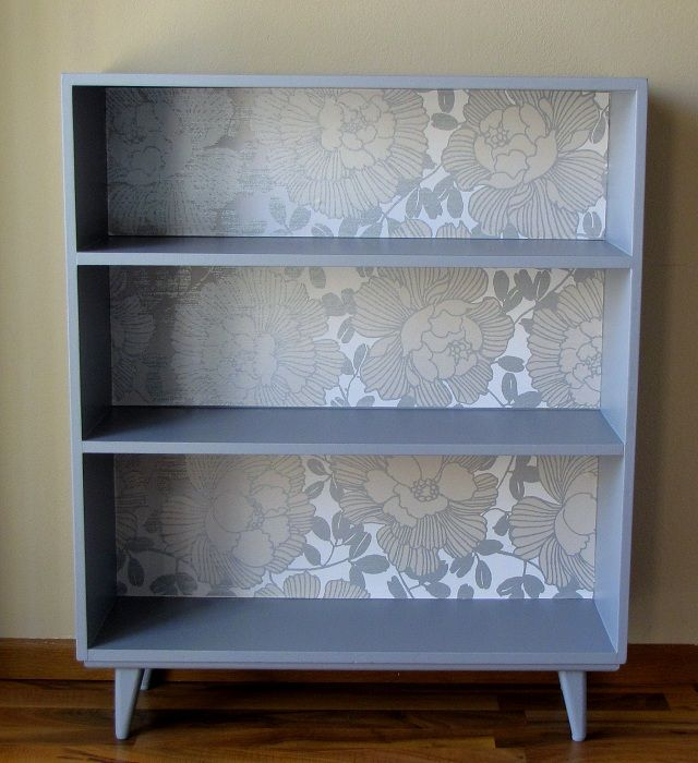 Do this to the shelving unit I have! get two basic bookcases, attach feet,  paint, back with cool wallpaper, and put on each side of desk for storage.