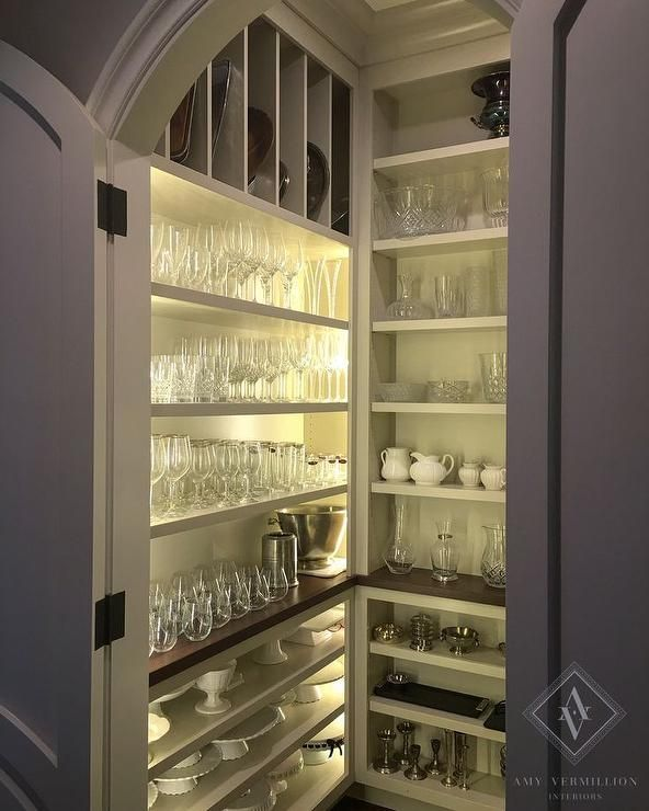An Arched Bi Fold Door Opens To A Small Chick Pantry Fitted With Vertical Tray Shelves And