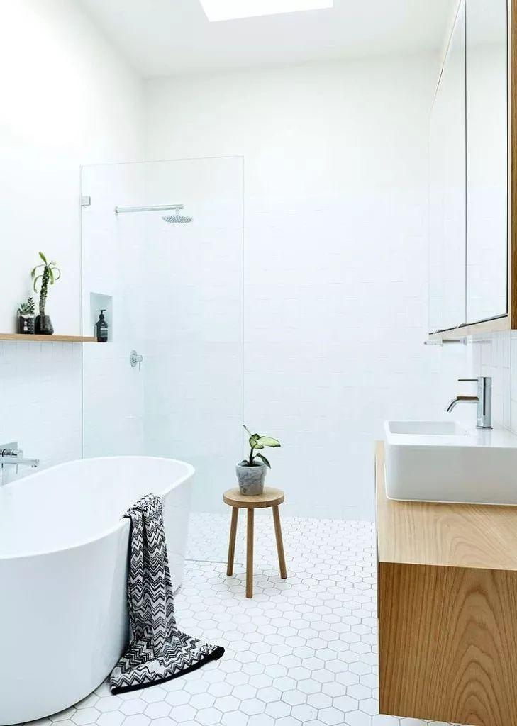 Un bagno totalmente bianco, con piastrelle esagonali sul pavimento e quadrate sulle pareti. Sono stati inseriti un mobile sospeso e una mensola sopra la vasca in legno chiaro per rompere il total white dell'ambiente