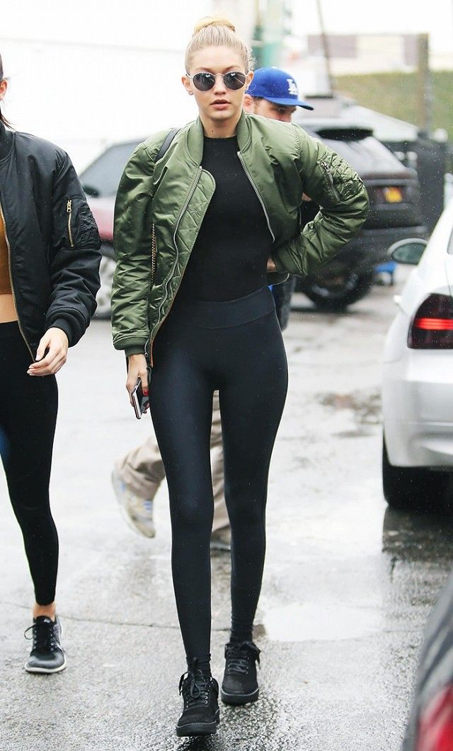 Gigi Hadid wears a bodysuit, leggings, olive green bomber jacket, round sunglasses, and black sneakers