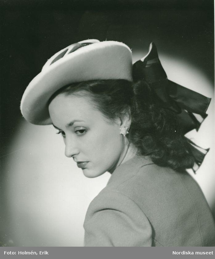 Från Claude S:t Cyr. Porträtt av kvinna i hatt med mörka dekorband baktill. Foto: Erik Holmén, 1946.