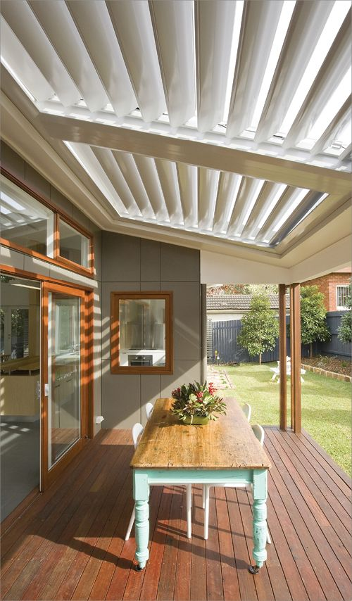 A wooden-decked verandah with louvred roof, allowing light to be directed inside the home.