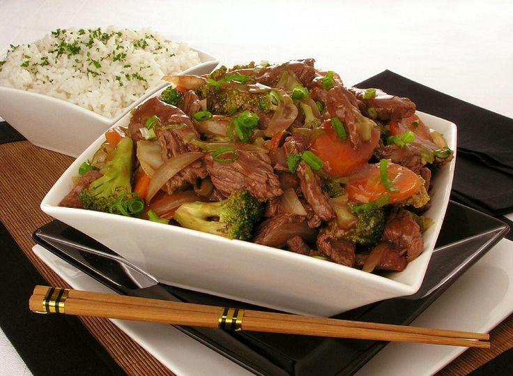 Na foto, a receita de carne com legumes e shoyu está disposta em uma tigela quadrada de vidro branco. Ao fundo, em outra tigela, está arroz branco. Toda a decoração da foto tem inspiração oriental, nas cores branca, preta e marrom.