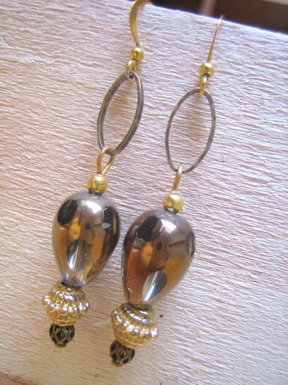 Glass & brass beads with a retro feel evoke the future of space travel in their resemblance to small space ships as they dangle gently from small brass oval loops! Nickel free 18k gold plated fish hook ear wires make these interesting pieces easy to wear, and stoppers are included to keep earrings firmly in place.  $20.00