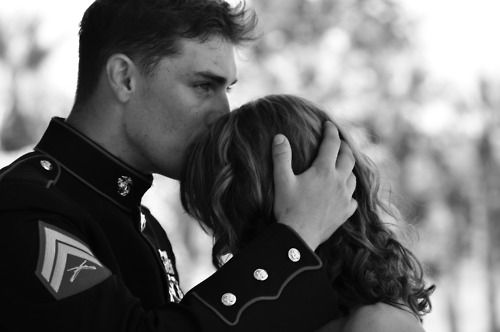 a united states marine saying goodbye to his girlfriend/wife before he leaves for duty.