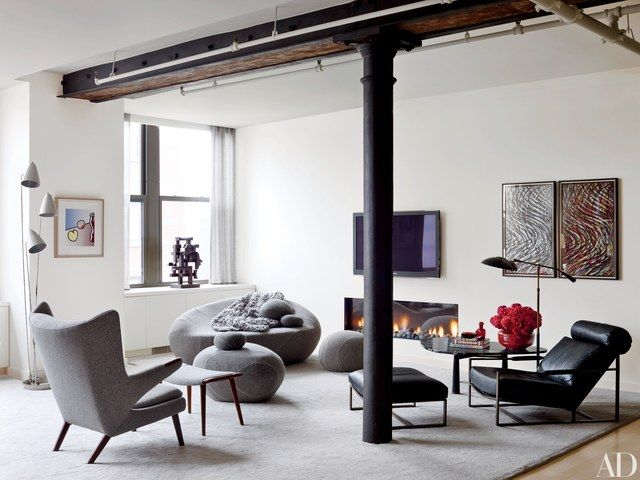The New York apartment of actor Will Ferrell and his wife, auctioneer Viveca Paulin-Ferrell, was renovated by architect Richard Perry and decorated by Shawn Henderson. The living room's boulderlike seating is by Smarin, and the Hans J. Wegner wing chair and ottoman are covered in a Zimmer + Rohde fabric. The artworks include, from left, a Roy Lichtenstein print, a Mario Dal Fabbro sculpture from Maison Gerard, and two Sol LeWitt woodcuts; the television is by Samsung.