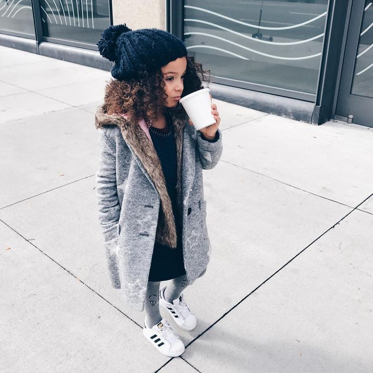 Kid layered fall fashion. Long grey trench coat, black beanie, black yes and jeans with adidas