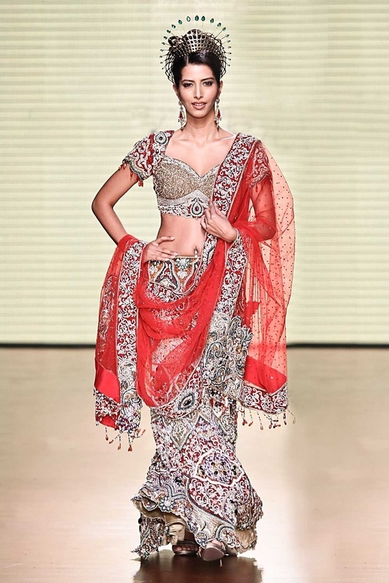 Satya Paul  Gold fish cut beautifully encrusted lehenga with stones and sequins work in an ornamental pattern. Comes with a red net dupatta by mandy