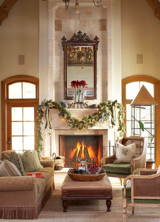 A dramatic stone fireplace is decorated with red amaryllis for Christmas garland on fireplace
