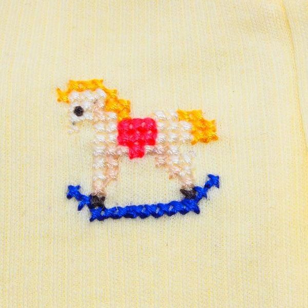 $18.00      Rocking Horse  Size 00000  Lemon Yellow lightweight full leg bodysuit/sleeper.  Soft and comfy, this suit is hand stitched with a cute little white rocking horse.  Would easily suit a baby boy or girl, as it has lovely neutral colourings.  Cotton, low fire danger. Lovely soft and stretchy fabric – like a T-shirt. Ideal for between seasons.  Wear as a playsuit during the day – or as pajamas at bedtime – your choice.  Would make a great baby shower gift, especially if baby's sex is…