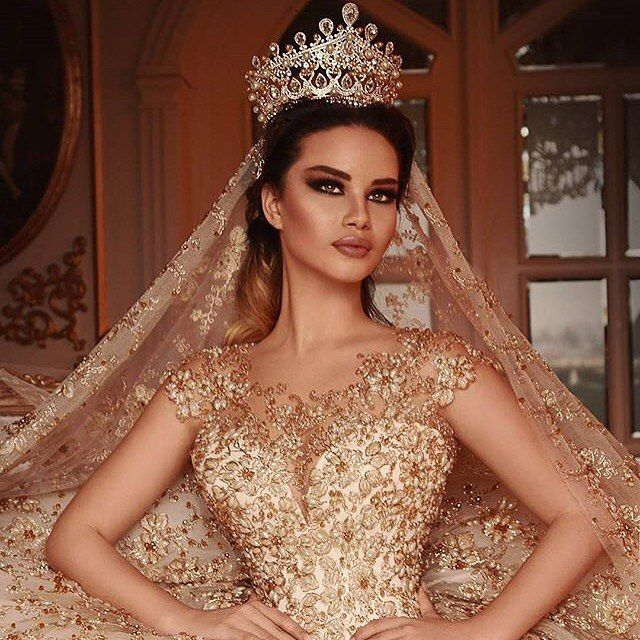This bride is stunning in this heavily embellished couture wedding gown. The beading and attention to detail is amazing. Haute couture wedding dresses like this will definitely cost many thousands of dollars.  But as American dress makers we can produce a similar look for a lot less.  We are a USA based design firm that specializes in inexpensive replicas of haute couture fashion pieces that are very similar to the original but cost much less.  Get pricing on custom wedding dresses…