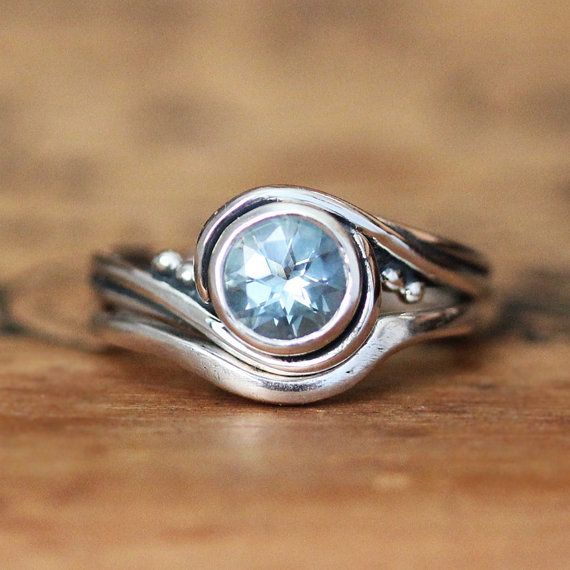 This unique aquamarine bridal set is handmade in my nyc studio and features a 6mm round aquamarine. This beautiful engagement ring set is inspired by a graceful, twirling ballerina, I call this my Pirouette ring setting. Cast into recycled sterling silver, a 6mm aquamarine is set into the center as the band curves up to swirl around the bezel. The matching band fits up next to the ring in a simple statement of love. This is a stunning ring set that will make you smile every time you look at…