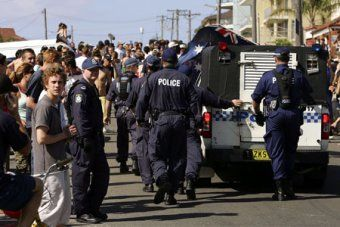 Tribunal rules Alan Jones incited hatred    Police officers escort a police vehicle through a crowd during unrest at Cronulla beach.