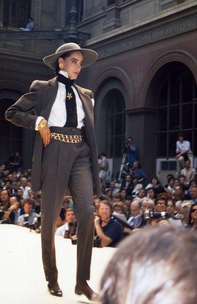 Modevisning. Modell i grå kostym, hatt och gulddetaljer. Från Chanel.