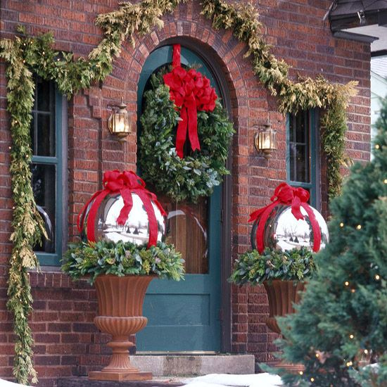 Wrapped in bright bows, these garden orbs resemble oversize packages with their silver shimmer. Set them atop mixed-green wreaths (that match the wreath on the front door) to elevate them in urns.
