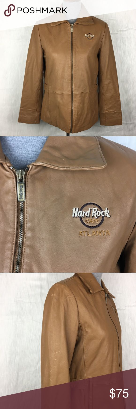 """Hard Rock Cafe 100% Leather Cognac Jacket hard rock cafe atlanta brown 100% leather jacket. adjustable buckles on the waist. two pockets. zip up front. embroidered logo on the chest. animal print lining.  size: women's medium  measurements: bust 19"""" across / length 25"""" / sleeve inseam 17"""" washing instructions: leather or suede expert flaws: marks from wear throughout, see photos discounts: 10% off bundles of 2 items and 15% off bundles of 3+ items Vintage Jackets & Coats"""