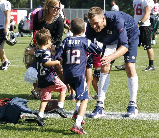 CaptionNew England Patriots quarterback Tom Brady waits as his sons, John Moynahan, center, and Benjamin Brady, left, run to him following the Patriots' joint workout with the Tampa Bay Buccaneers at