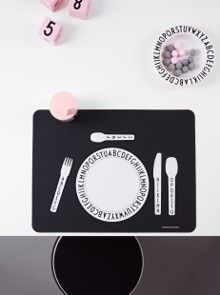 Eat, Play and Learn. Cool kids table setting with black place mat in silicone and melamine tableware. Drink lid for the smallest children and wooden cubes featuring Arne Jacobsen Vintage ABC numbers.