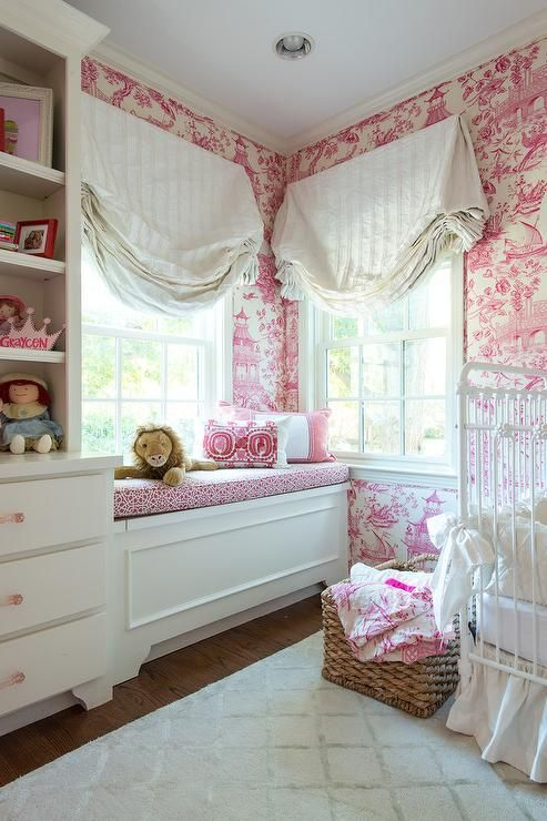 White and pink nursery features walls clad in pink toile wallpaper lined with a white metal French crib dress in ruffled bedding and bow ties.
