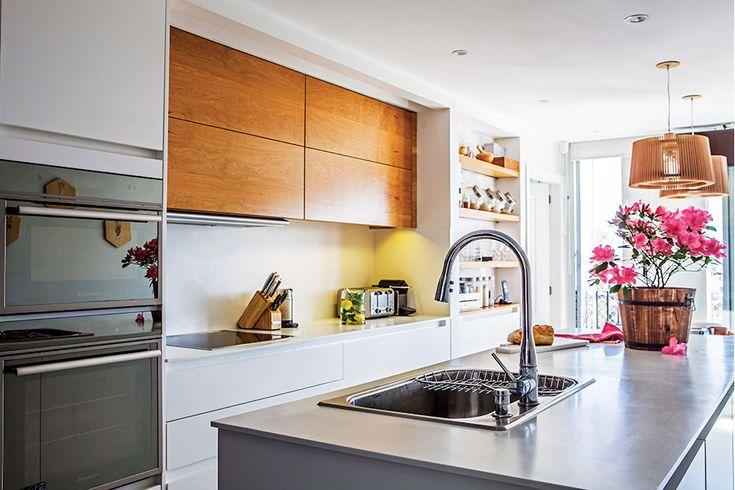 En la cocina de este departamento, muebles de líneas netas, sin molduras ni herrajes. Las alacenas están enchapadas en madera y esconden el filtro del extractor.