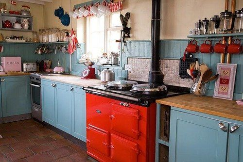 Adorable country kitchen - red checkered curtains, open shelves. I really like the blue cupboards too. Click through for more photos.