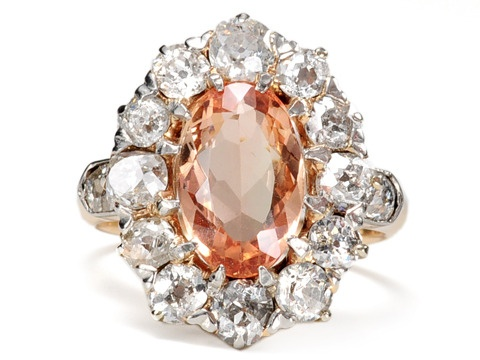 Antique Imperial Topaz Diamond Cluster Ring, 2 carat oval topaz in a Victorian cluster setting of silver topped 14k yellow gold. Surround of 1 old European cut and 11 old mine cut diamonds. Shoulders accented with additional old mine cut diamonds bringing a total estimated carat weight of 1.1 carats, J-K color/SI1-2 worth of diamonds. Circa 1880