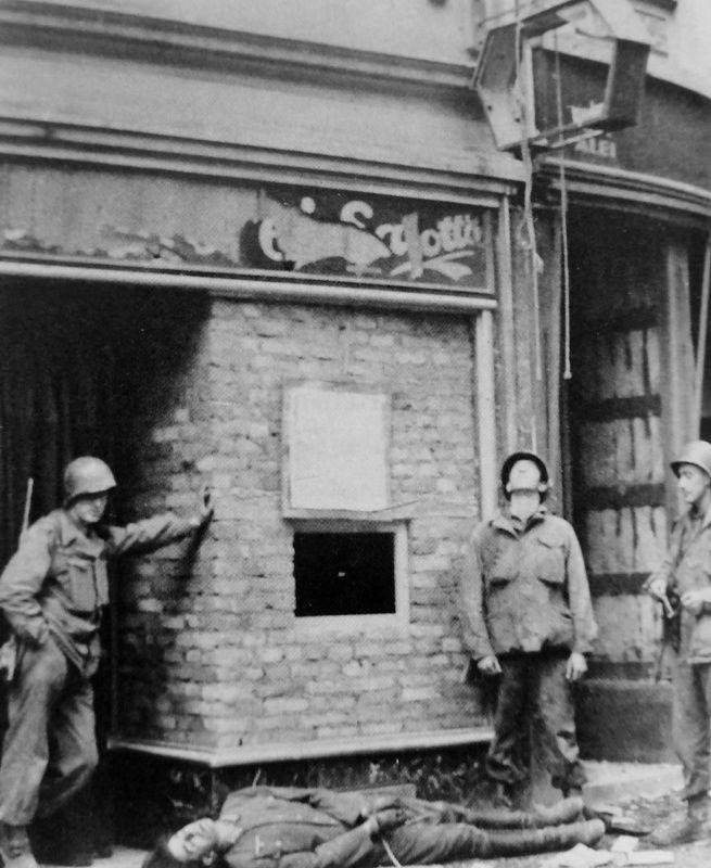 Американские солдаты у тела повешенного военнослужащего вермахта в немецком городе
