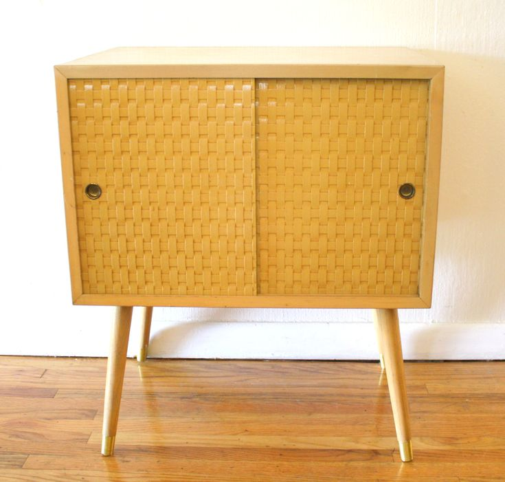 mid century modern side table with basket weave doors this is a mid modern side table with basket weave sliding doors it has the signature mcm legs and a
