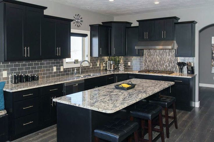 Contemporary kitchen with black cabinets, island and giallo verona granite count… ,