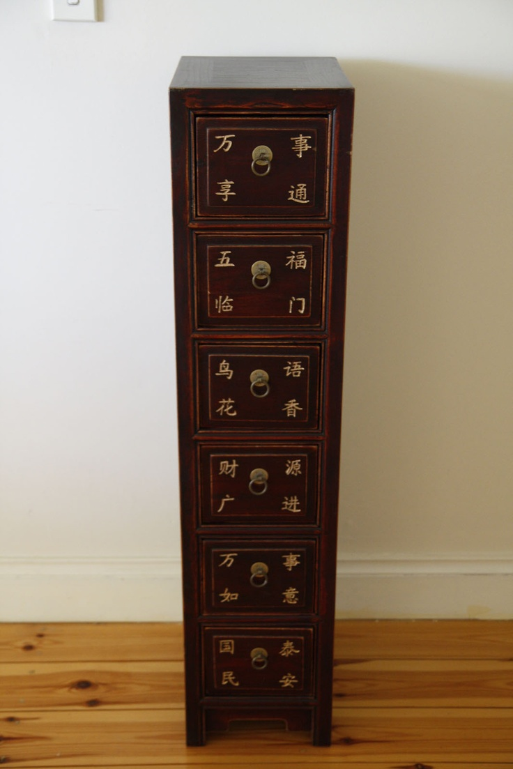 Quintessential Chinese decorating always starts with a cabinet of some description. Our traditional style medicine cabinet made from elm, features elegant Chinese writing on the drawer fronts and a warm brown finish. Its slim profile makes it ideal for small spaces or lifeless corners. Features      Cabinet is a reproduction item made from elm with a dark stained variegated finish.     Engraved Chinese script on drawer fronts     6 drawers with antique brass hardware.     Asian Style