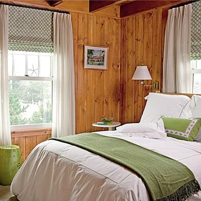 Natural wood details contrast with crisp green and white accents in this guest bedroom. The room's understated elegance calls attention to its beamed ceilings and knotty pine walls, ceilings, and floors. coastalliving.com