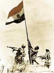 Egyptian soldiers raise the Egyptian flag on Bar-Lev line bunker in Sinai 6th of October 1973