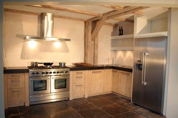Een landelijke keuken met een warme uitstraling. De houten steunbalken en de RVS keukenapparatuur maken het plaatje helemaal compleet.