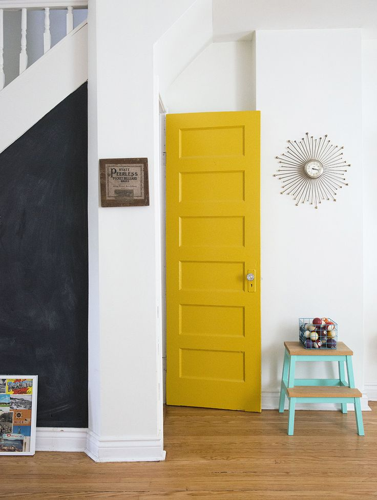 Since all the walls in the house are painted white, Catherine added some pops of color elsewhere to liven things up. This yellow door adds so much cheer to the room. The couple also painted a chalkboard under the stairs where they leave eachother messages, doodle when the mood strikes, or work out the occasional math problem.